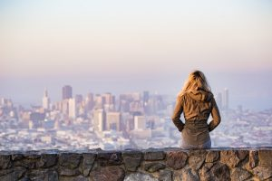 A woman sitting on an edge looking at the city.