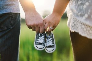Parents holding baby shoes.